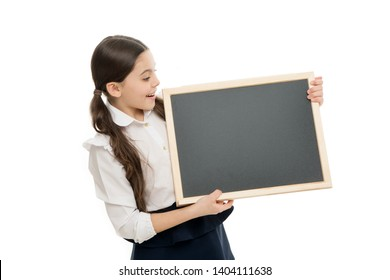 The beginning of the lesson. Little schoolgirl holding blank blackboard for private lesson. Small pupil learning lesson at school. Adorable little child reciting a lesson at blackboard, copy space.