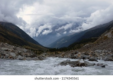 Beginning of the Lonze river as melting water from the Lang Glacier in Lotschental during bad weather with plenty clouds