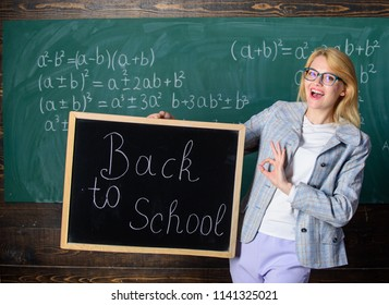 Beginning of new school season. Woman teacher holds blackboard inscription back to school. Are you ready to study. Lady educator in classroom wonders you ready to study. Teacher welcomes school year.