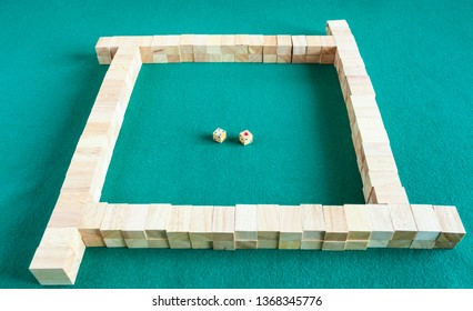 beginning of play in mahjong, tile-based chinese strategy board game on green baize table