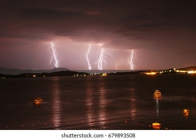 Beginning of a storm in a sea  with lightnings in purple sky. Yachts and boats parked in a bay.
