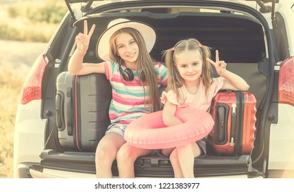 beginning of the trip. Little cute girls in the trunk of a car with suitcases