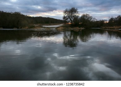 Beginning of winter, beautiful landscape with trees by the river at sunset