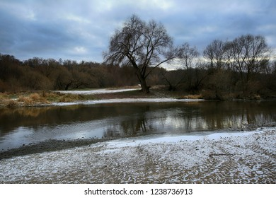 The beginning of winter, the first snow, a beautiful landscape with trees by the river at sunset