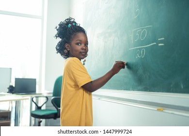 Beginning to write. Smiling school girl holding chalk close to the blackboard thinking what to write.