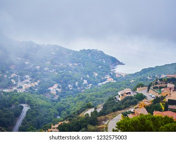 Begur, Spain - September 15, 2018. Sa Riera of Begur mountains in the fog with the Platja de Sa Riera beach in the background. View from the Castle of Begur. Girona, Costa Brava, Catalonia, Spain.