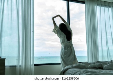 Behide asian woman in bathrobe suit open curtain to see view outside in morning, Travel and Holiday concept