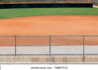 Behind amateur baseball field chain link fence. Blurred background showing part of dirt infield and grassy outfield.