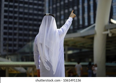 behind of the arab man point upper  with modern city background . Behind arab man pointing to the sky . Back view of arabian businessman standing and point to the modern building