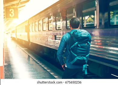 Behind asian young man standing and waiting train on platform.