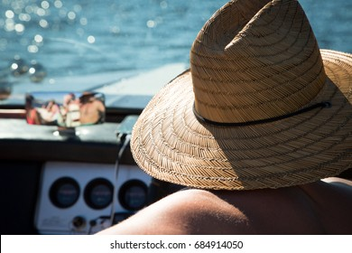 Behind the back over the shoulder close up rear perspective of male boat captain sitting in drivers seat of motor wearing wide brim woven straw sun hat without shirt with glinting sunlight on water