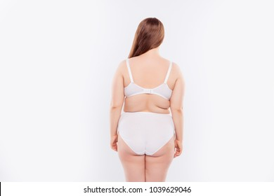 Behind back rear view photo of oversized overeating chubby obese positive woman clothed in white compression garments, she has flawed sagged fat folds, isolated on white background