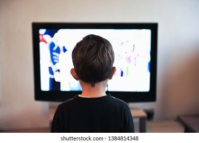 Behind the boy Standing looking at cartoons on TV