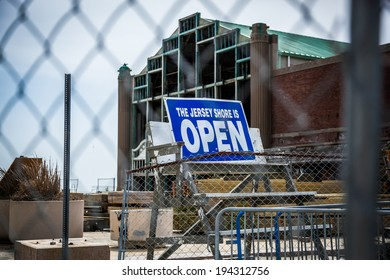 """Behind a chain link fence, a sign stands reading """"The Jersey Shore is Open."""" Photo taken in April, 2013 in Asbury Park, NJ. You can see signs of reconstruction as they rebuild from Hurricane Sandy."""