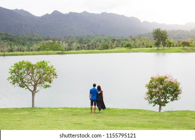 Behind of couple with full nature grass field , lake , mountain and tree . Romance seen