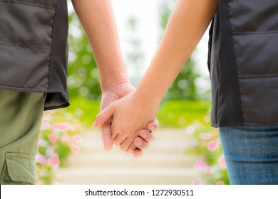 Behind of a couple holding hand in the garden with warm light. Love and background. Romantic love concept. Copy space.