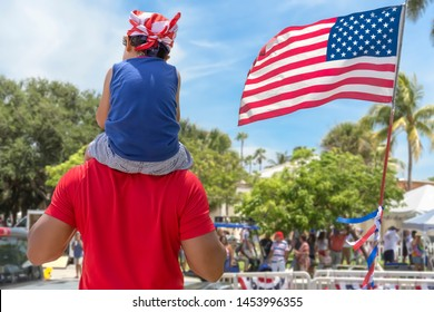 From behind a father carries his young son on his shoulder celebrating American with the community. The son wearing a flag bandana on top of his dad's shoulder passing by the American flag.