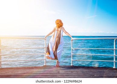 Behind girl on pier. A woman admires the beautiful views of the ocean on the pier at the railing.