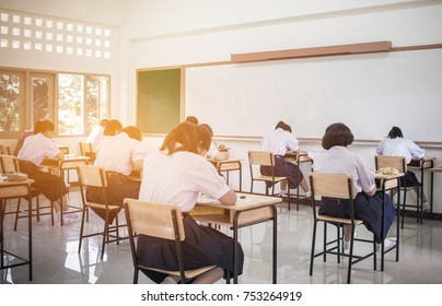 Behind girls group undergraduate students testing of examination in room and student sitting on row chair doing final exams in classroom with Thailand uniform. Asian Education Concept.