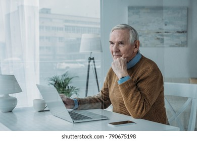 Behind the glass view of senior confident man working on laptop