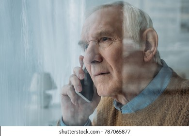 Behind the glass view of senior disturbed man making a phone call