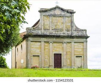 behind the green hill stands a small historic country church in neoclassical style