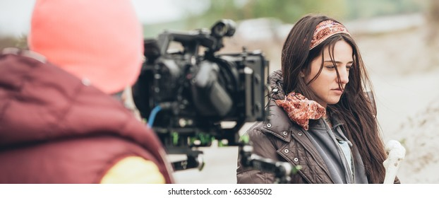 Behind the scene. Actress in front of the camera on the film set outdoor location. Group movie scene