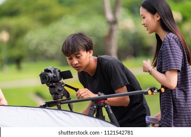 Behind the scene. Asian Cameraman and assistant shooting the film scene with camera on outdoor location.