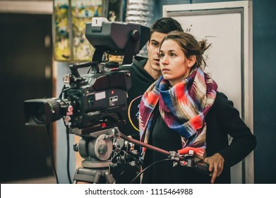 Behind the scene. Cameraman and assistant shooting the film scene with camera in film studio