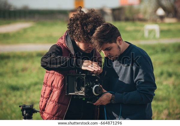 Behind the scene. Cameraman and assistant shooting the film scene with camera on outdoor location
