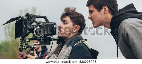 Behind the scene. Cameraman and film director shooting film scene on outdoor location