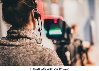 Behind the scene. Female cameraman shooting the film scene with camera in film studio