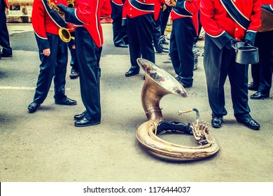 Behind scene. Golden sousaphone resting on ground while members of marching band, dressing in uniform of red jacket, black pants, leather hats, shoes, standing around, preparing for parade in New York