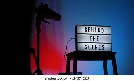 Hinter den Szenen Buchstaben Text auf Leuchtkasten oder Cinema Light Box. Mehrfarbige LED auf dem Hintergrund. Sillhouette Blitz Snoot Kapuze auf Stativ. Videoproduktionsstudio. Hinter dem Leuchtkasten