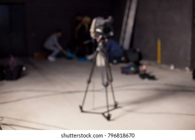 Behind the scenes or making of film in the studio and silhouette of cameraman, blurred image. blur image of group of stage staff for background usage. Video camera is ready to record.