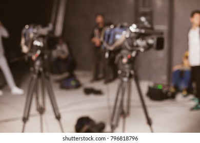 Behind the scenes or making of film in the studio and silhouette of cameraman, blurred image. blur image of group of stage staff for background usage. Vintage photo processing