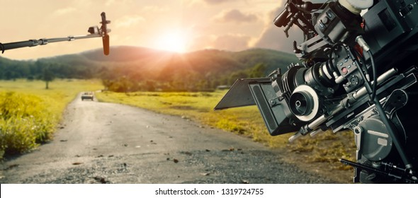 Behind the scenes making of movie and TV commercial. Camera of movie and video production. Film Crew. B-roll, and crew team in outdoor nature background.