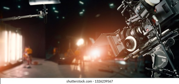 Behind the scenes of making of movie and TV commercial. Camera of movie and video production. Film Crew. B-roll, with crew team in studio and set on dark background.