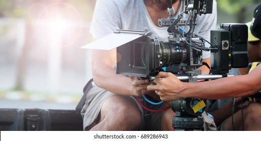 Behind the scenes of movie shooting or video production and film crew team with camera equipment at outdoor location.