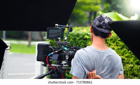 Behind the scenes of movie or video shooting production camera set and film crew at outdoor location.