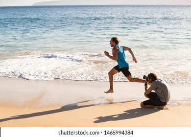 Behind the scenes of photo shoot of male sports athlete model running for photographer taking pictures for sport photoshoot. BTS on beach.