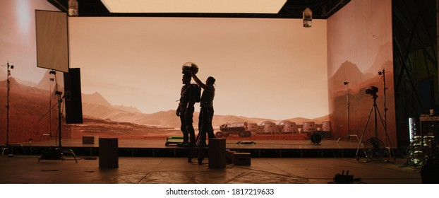 Behind the scenes shot of virtual production stage with huge LED screens, cinematorgapher shooting Mars scene. Future of movie production - Shutterstock ID 1817219633
