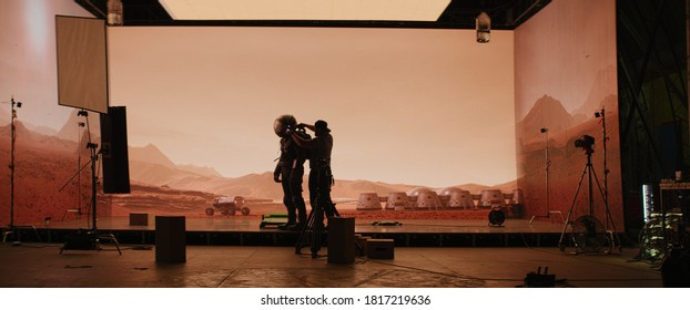 Behind the scenes shot of virtual production stage with huge LED screens, cinematorgapher shooting Mars scene. Future of movie production - Shutterstock ID 1817219636
