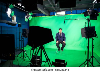 Behind the scenes of TV movie video film shooting production crew team and camera lighting set in the big studio , A television presenter in a TV studio with a camera and lighting equipment