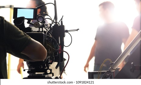 Behind the scenes of video production in the big studio with professional equipment such as camera tripod and crane.