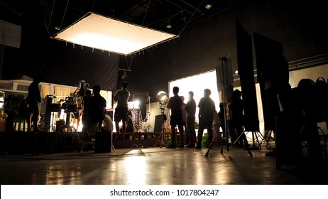 Behind the scenes of video shooting production crew team silhouette and camera equipment in studio.