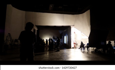 Behind the shooting of video online commercial production and film crew team working and setting light or camera or soft box and equipment set up in big studio in silhouette style