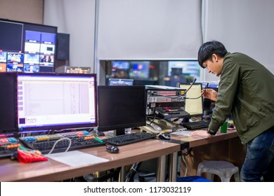 Behind the televised broadcast in the control room, live in the control room. Producer looking at the chart list on the table.