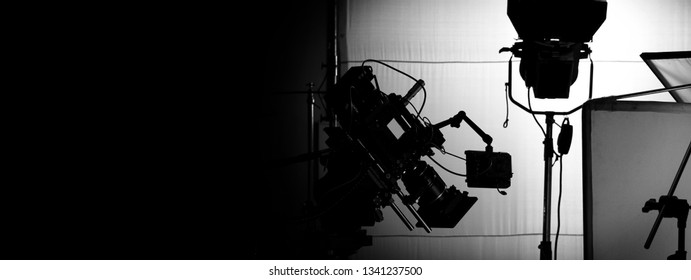 Behind video camera in film or movie production on tripod and professional gear which shooting in location or studio with crew team and prop or set and ready to online live broadcast or tv on air