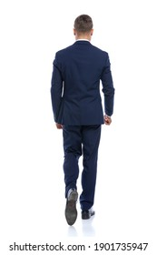 behind view of elegant young man in navy blue suit walking isolated on white background in studio